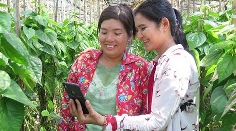Two women look at a smartphone. Photo credit: UNCDF