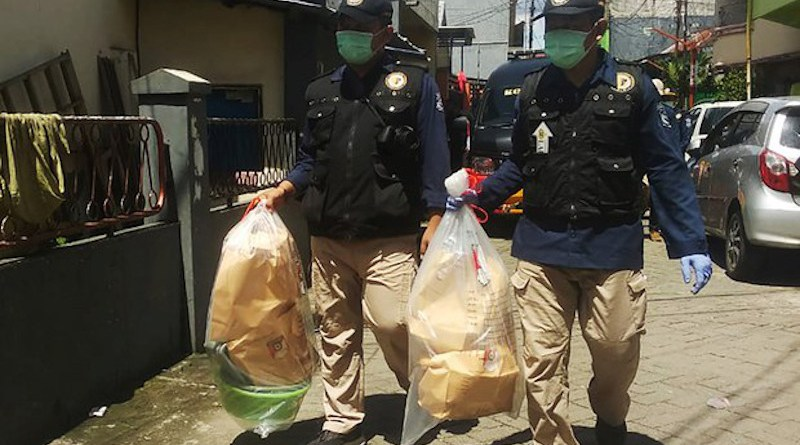 Two police officers carry plastic bags containing items recovered from the Makassar-area home of a couple suspected of carrying out a suicide bombing outside a church in Makassar on Palm Sunday, March 29, 2021. Yayank Stiv/BenarNews