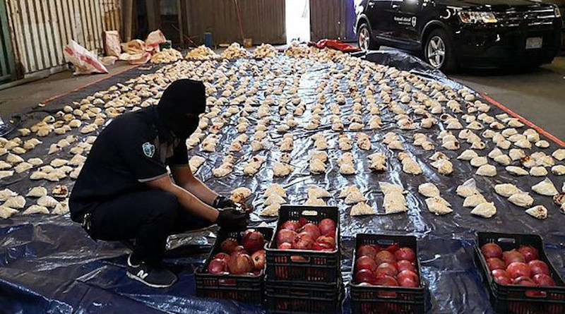 A Saudi custom officer opens imported pomegranates, as customs foiled a attempt to smuggle millions of Captagon pills, which came from Lebanon, at Jeddah Islamic Port on April 23, 2021. (SPA)