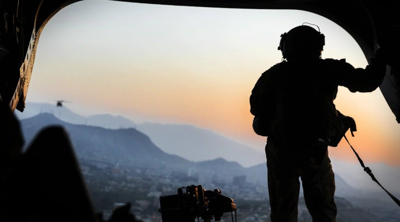 Army loadmaster stands on the rear ramp of a CH-47F Chinook and watches the sunset as the helicopter flies over Kabul, Afghanistan. Photo Credit: Julie A. Kelemen, DOD
