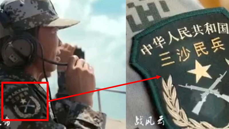 """A """"Sansha Militia"""" patch visible on the sleeve of a militiaman carrying out surveillance from a militia post. Credit: Political Department of the PLA Hainan Province Sansha Garrison."""