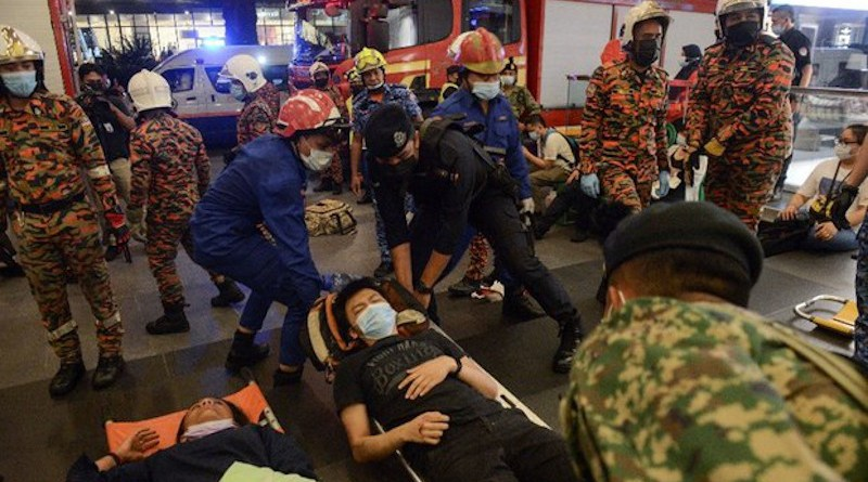 Malaysian search-and-rescue personnel move an injured passenger from a train crash into an ambulance in Kuala Lumpur, May 24, 2021. S. Mahfuz/BenarNews