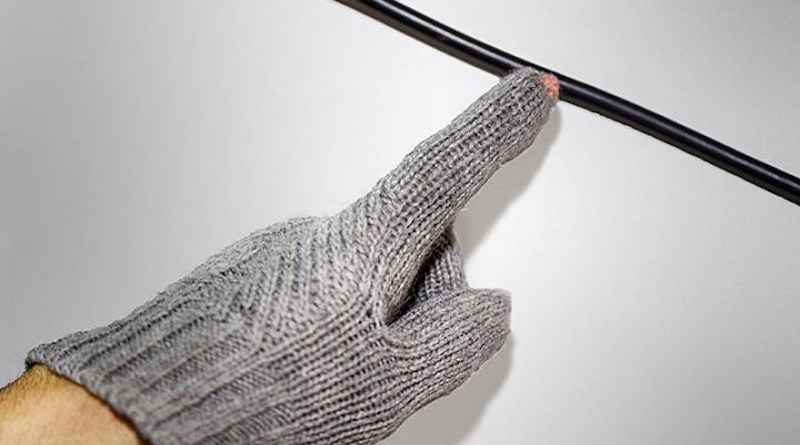 The fingertip of a wireless voltage detection glove illuminates when the wearer's hand approaches a live cable. Purdue University engineers have developed a method to transform existing cloth items into battery-free wearables resistant to laundry. CREDIT (Purdue University photo/Rebecca McElhoe)
