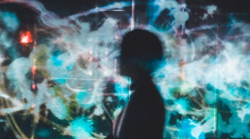 Human figure in front of digital screens. TeamLab Japan (Tokyo, Japan). Photo: Su San Lee (@blackodc) at Unsplash