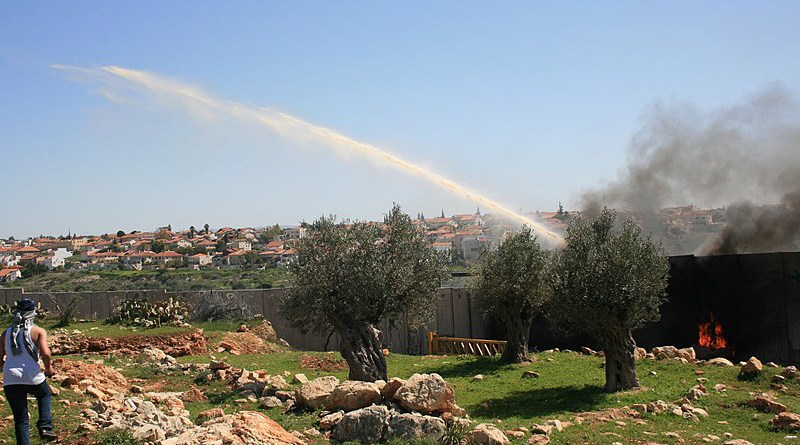 File photo of Israeli forces launching Skunk 'water' against demonstrators. Photo Credit: יורם שורק, Wikipedia Commons