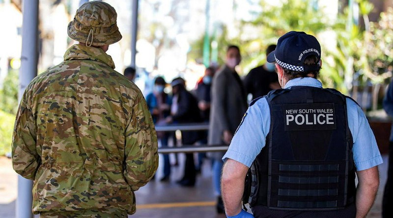 An Australian Army soldier and NSW Police Constable observe Covid-19 Vaccine operations at the Marana Auditorium in Hurtsville as part of the NSW Operation COVID-19 Assist. Photo credit: Corporal Dustin Anderson