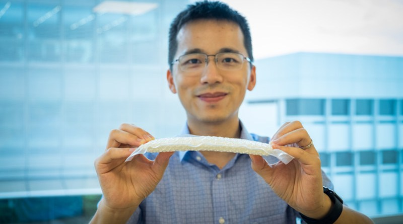 NTU Asst Prof Wang Yifan bending the nylon chain mail, encased in a plastic envelope and vacuum-packed, which makes it 25 times stiffer than usual. CREDIT: NTU Singapore