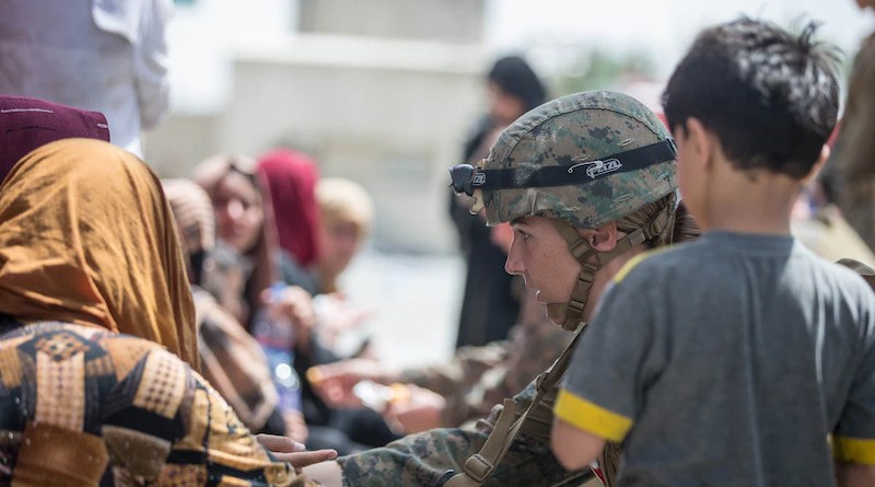 A Marine checks the well-being of evacuees at Hamid Karzai International Airport, Kabul, Afghanistan, Aug. 20, 2021. U.S. service members are assisting the Department of State with an orderly drawdown of designated personnel in Afghanistan. Photo Credit: Marine Corps Sgt. Samuel Ruiz