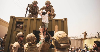 U.S. Marines, along with British and Turkish forces assist a child during an evacuation at Hamid Karzai International Airport, Kabul, Afghanistan, Aug. 20, 2021. U.S. service members are assisting the Department of State with a non-combatant evacuation operation (NEO) in Afghanistan. Photo Credit: Marine Corps Staff Sgt. Victor Mancilla
