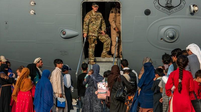 Service members prepare to board evacuees onto a C-17 Globemaster lll at Al Udeid Air Base, Qatar, Aug. 22, 2021. Photo Credit: Air Force Airman 1st Class Kylie Barrow