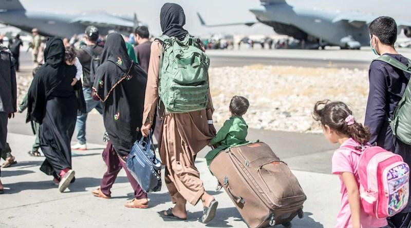 Afghan civilians walk towards an aircraft at Hamid Karzai International Airport, Kabul, Afghanistan, Aug. 24, 2021. Photo Credit: Marine Corps Sgt. Samuel Ruiz