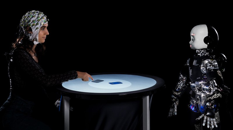 """Illustration of a human and a humanoid robot engaged in a competitive game, as reported in Belkaid et al. """"Mutual gaze with a robot affects human neural activity and delays decision-making processes"""" (Science Robotics). The human is playing against the robot while her brain activity is being measured with electroencephalogram (EEG). CREDIT: IIT-Istituto Italiano di Tecnologia"""