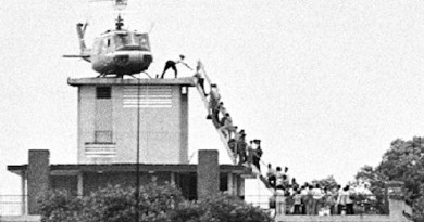 A member of the CIA helps evacuees up a ladder onto an Air America helicopter on the roof of 22 Gia Long Street April 29, 1975, shortly before Saigon fell to advancing North Vietnamese troops. Photo Credit: Hubert van Es, Wikipedia Commons