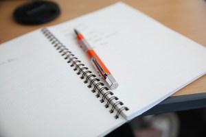 photographie d'un cahier ouvert et d'un stylo