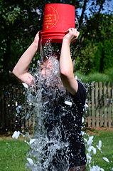 photo d'un homme se renversant un seau d'eau glacée sur la tête
