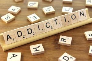 le mot addiction avec des lettres de Scrabble