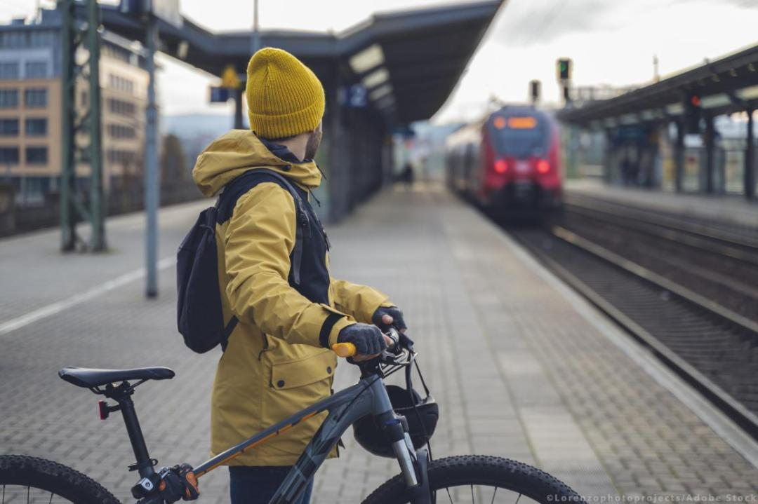 A man in winter clothes, waiting with his bike, the train. ©AdobeStock/Lorenzophotoprojects