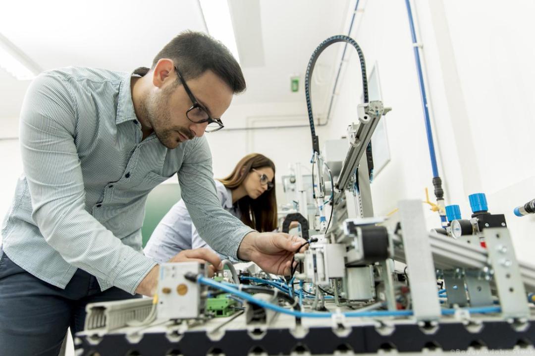 Engineering employee working in a robotics lab. ©AdobeStock/Boggy
