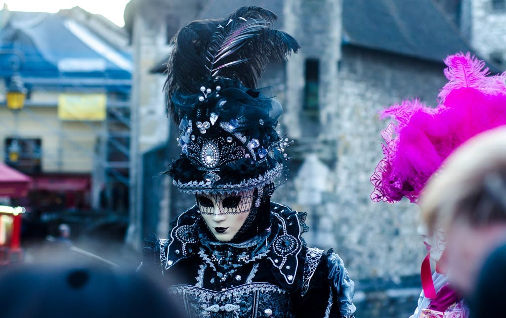 A masquerader in front of the Palais de l'Île