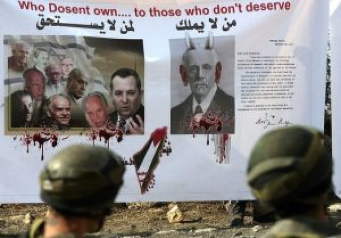 Israeli soldiers in front of a banner with a protesting against balfour (AFP)