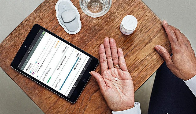 Pill with a digital sensor: in front of a table we can see a tablet, a glass of water, a pills box, and the hand of a man holding a pill