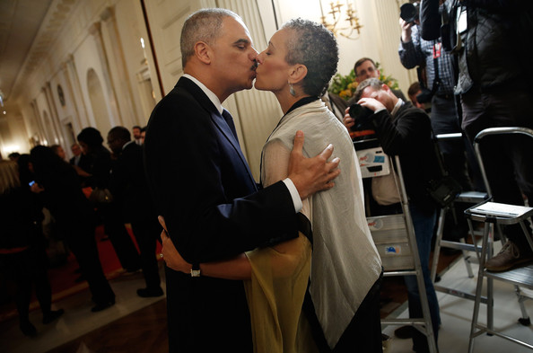 U.S. Attorney General Eric Holder (L) kisses his wife, Sharon Malone (R), after announcing his resignation at the White House September 25, 2014 in Washington, DC.