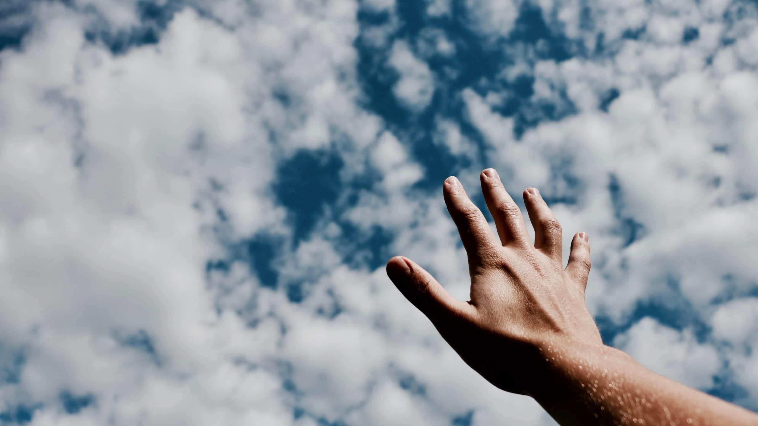 Mão para o alto com céu ao fundo