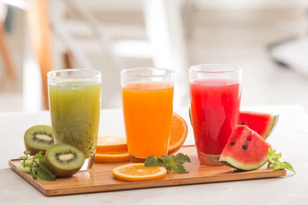 Três copos cheios de sucos. Um de kiwi, outro de laranja e o outro de melancia. Todos estão sobre uma bandeja de madeira decorados com pedaços das respectivas frutas.