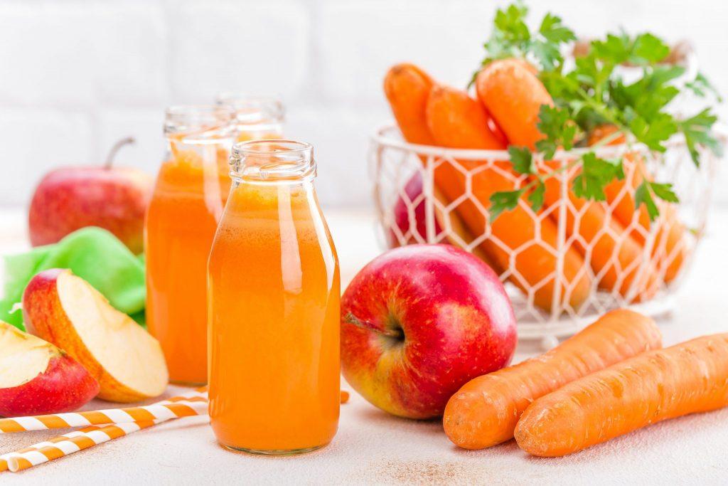 Três garrafinhas com suco na cor laranja. Ao lado, estão dispostas maças inteiras e cortadas, cenouras sobre a mesa e um cesto com cenouras e sasinhas.
