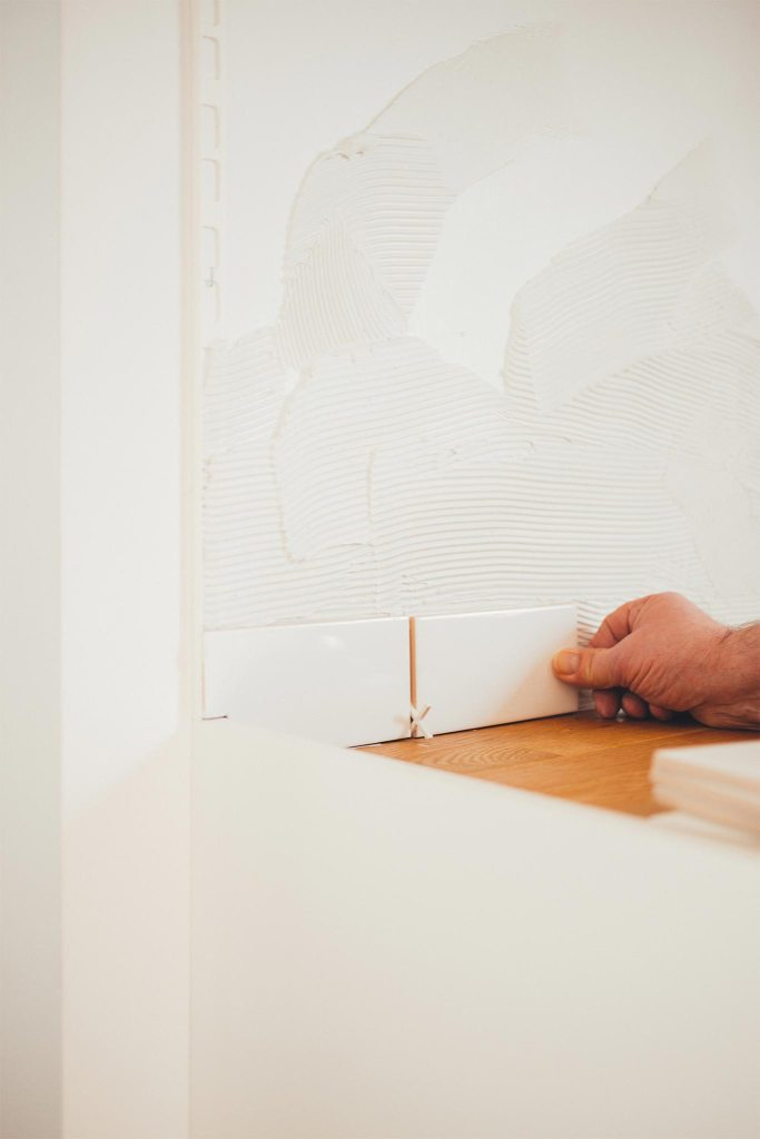 Eine Hand drückt Kacheln an eine Küchenwand
