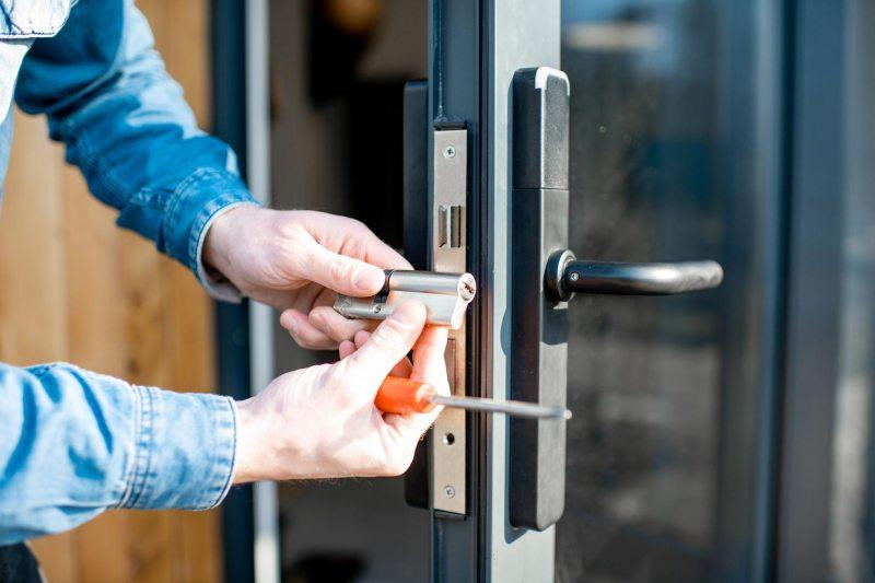 Ein Hausmeister repariert ein Türschloss