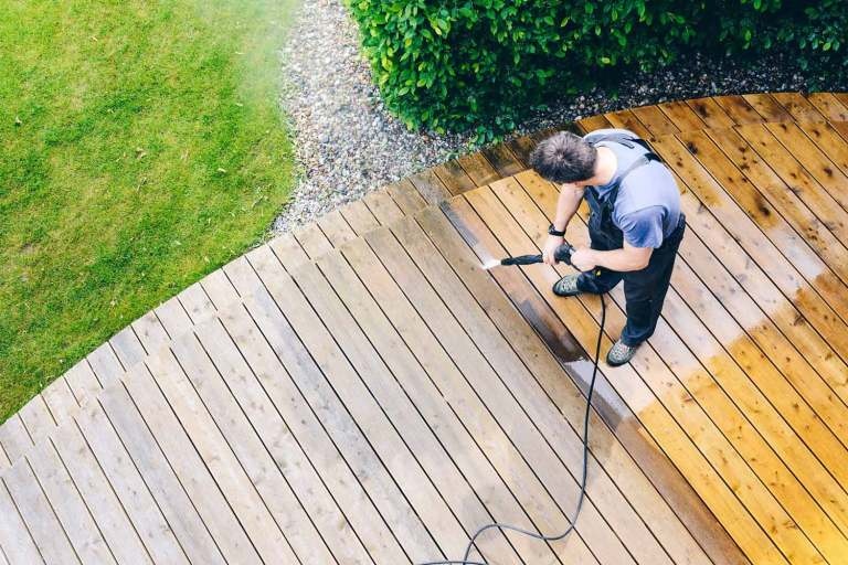 Ein Mann reinigt eine Terrasse mit einem Hochdruckreiniger