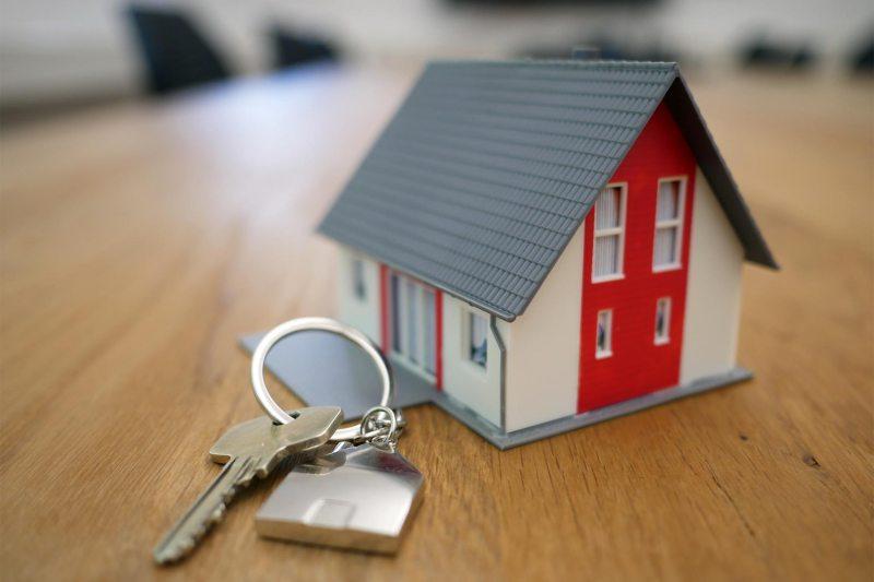 Ein Miniatur-Haus steht neben einem Schlüssel auf einem Schreibtisch