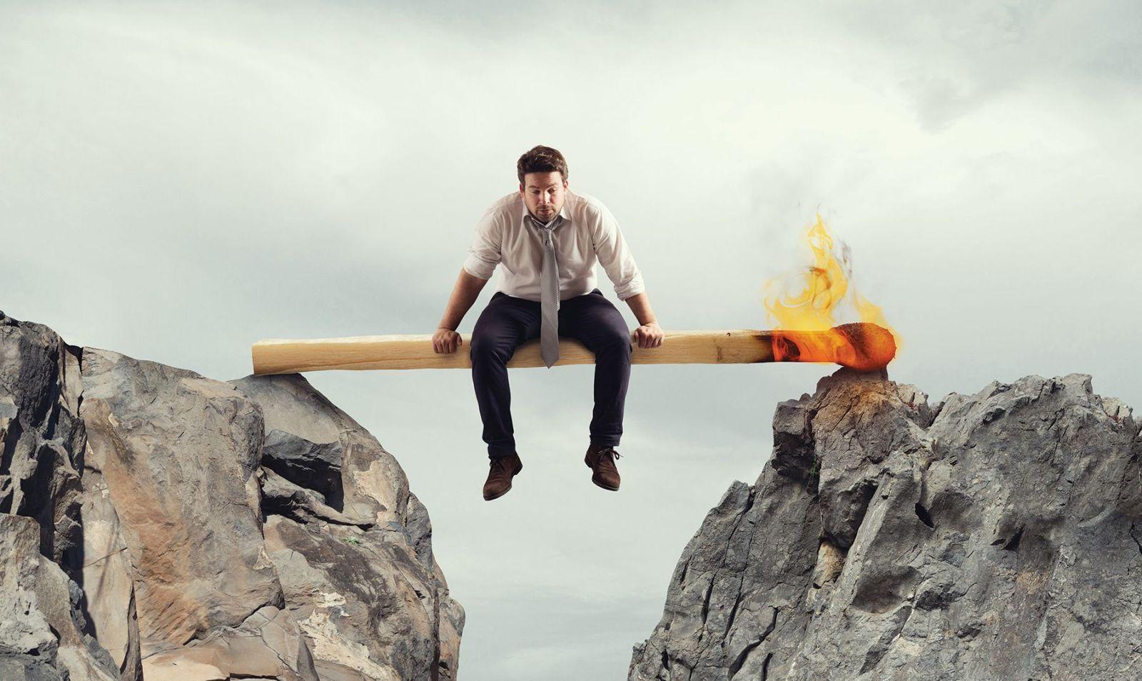man sitting on large burning match