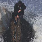 man on rock in waves