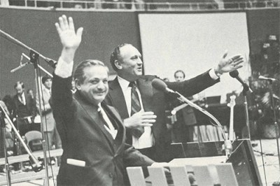 The Reverend Trandafir Sandru (left), Romanian church leader, was introduced by General Overseer Ray H. Hughes (right). After extending a warm greeting, Brother Sandru received a standing ovation.