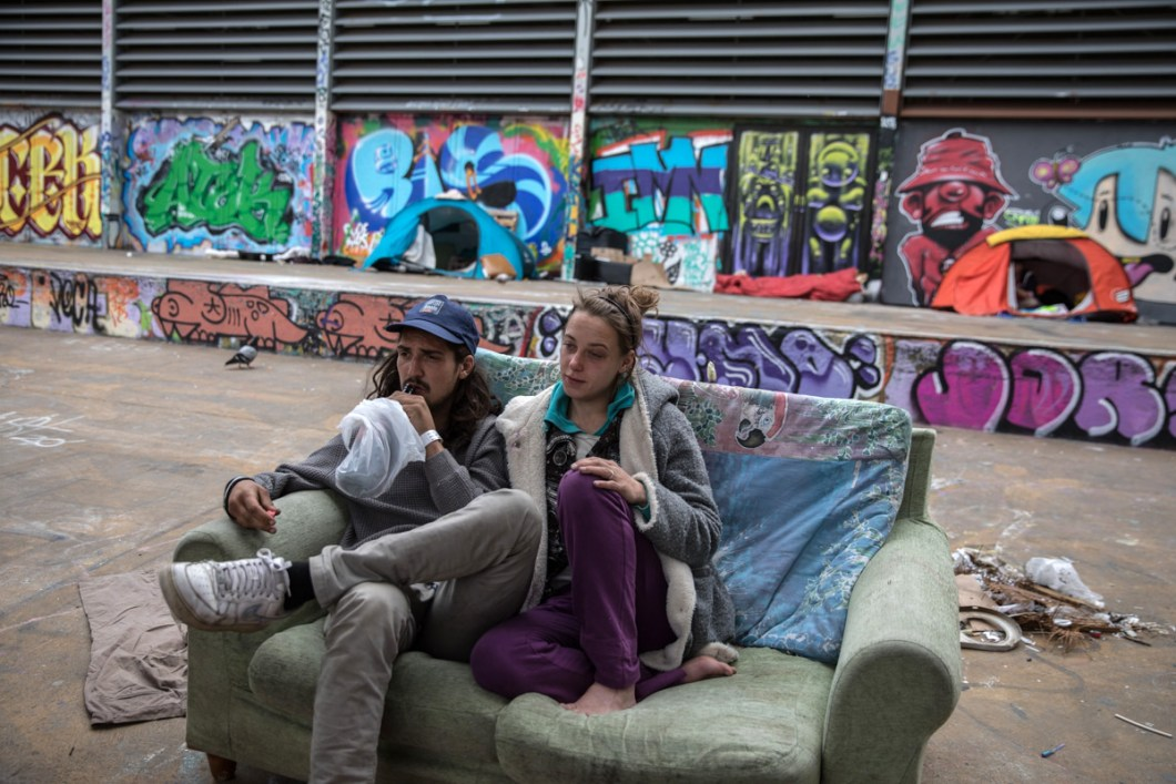 A couple from Sweden who has been living on the streets of Barcelona for 6 months, has settled during confinement in a square of the city center with a tent. They would like to be able to confine themselves to a shelter for homeless people, but they would be forced to be separated, he in a men's shelter and she in a women's one. So they prefer to sleep on the street together. Barcelona, March 27th. Photo by Eva Parey.
