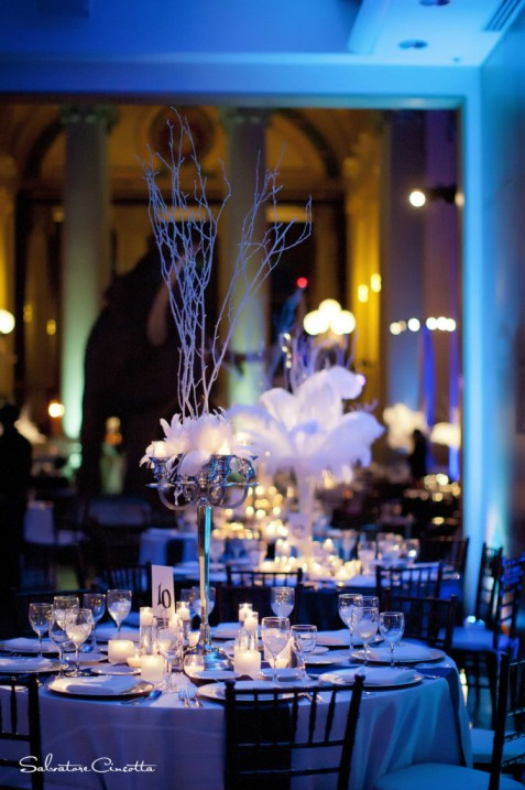 Wedding reception table with feather and twig centerpieces and blue lighting