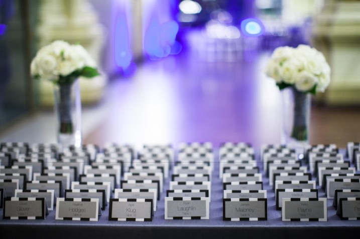 A table of lined up black and white striped escort cards for a wedding