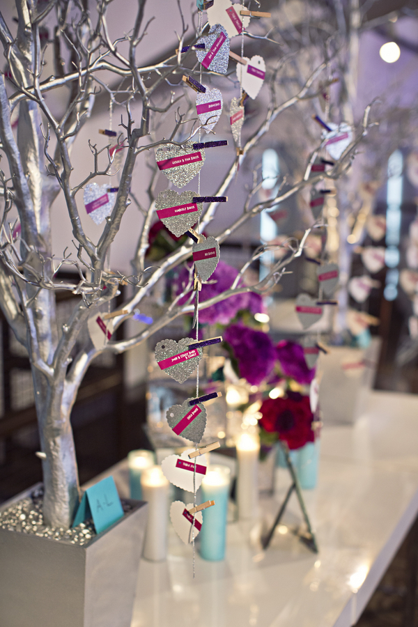 silver glitter heart escort cards hanging on silver potted tree with purple glitter clothespins