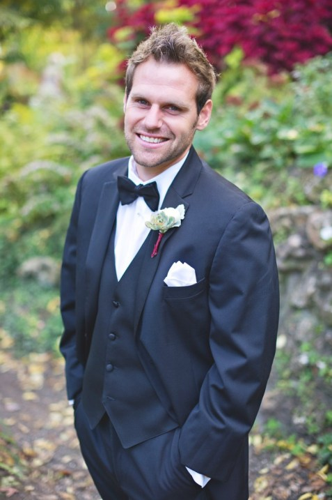 Groom in black tux and bowtie with succulent boutonniere