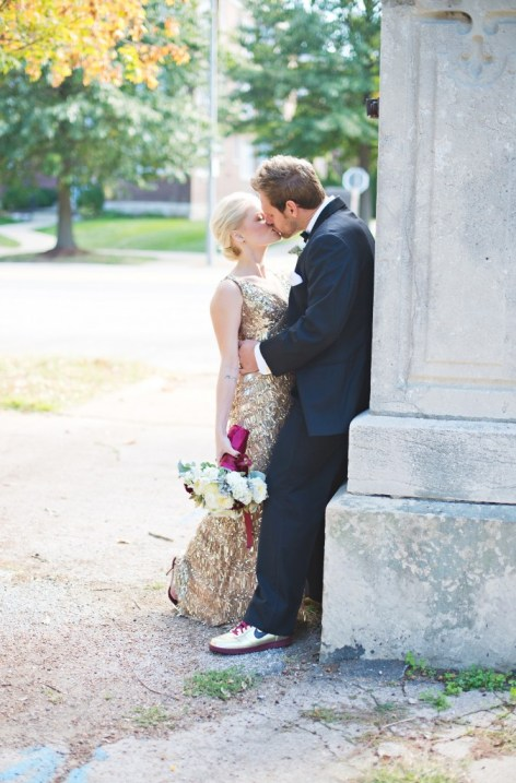 Bride and groom kissing at park gold sequin gown