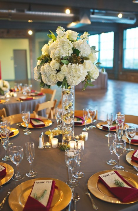 Tall white hydrangea and rose centerpieces on vase filled with lightbulbs
