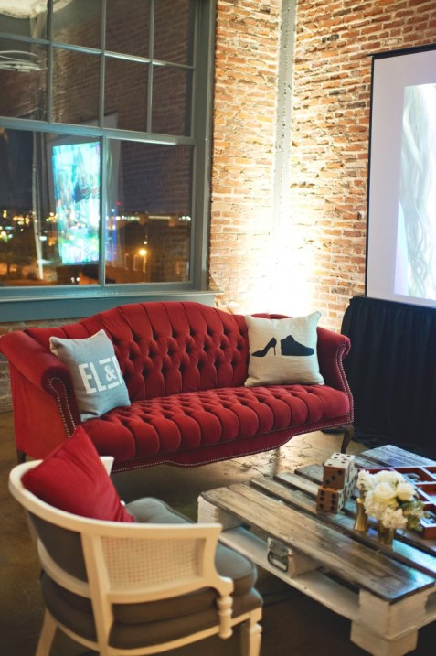 Dark red vintage couch with custom logo pillows wedding reception