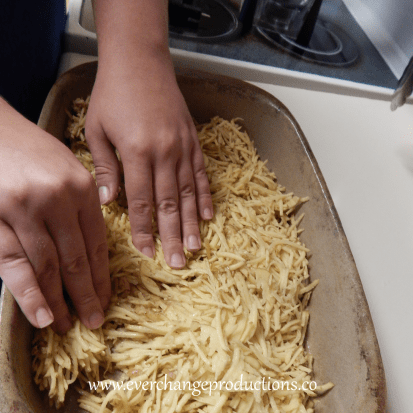 Step One of my favorite local recipe: shred potatoes and layer them in pan.