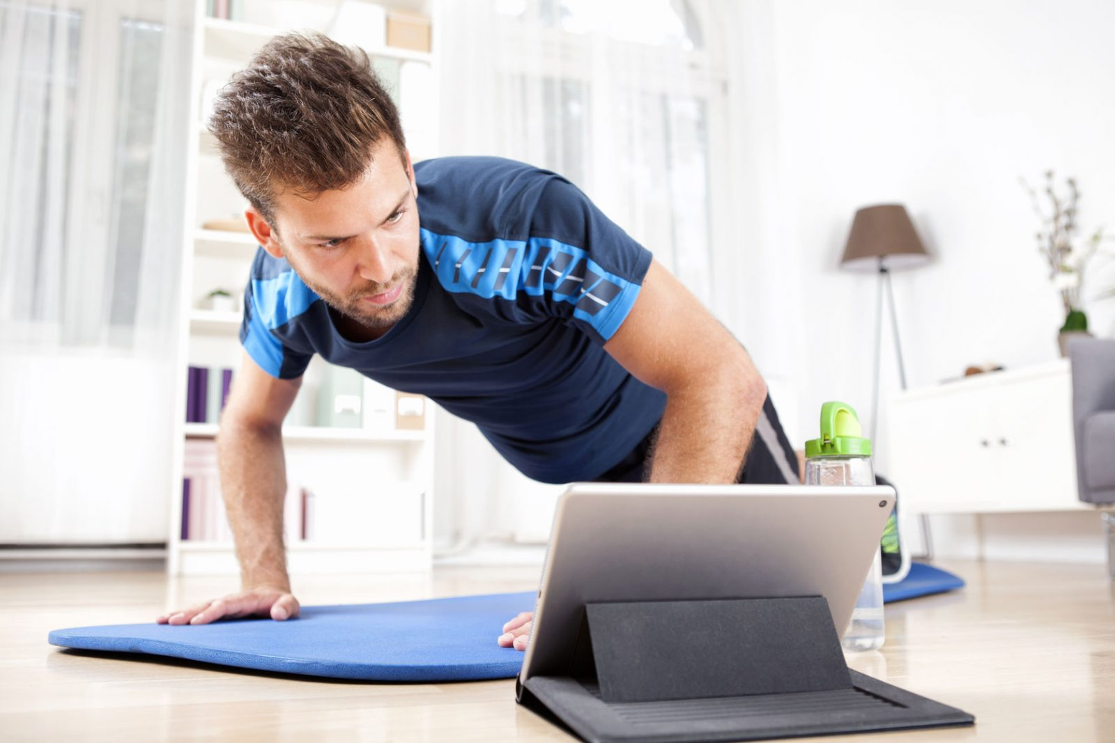 51546198 - athletic young man doing a planking exercise at home while watching movie on his tablet computer.