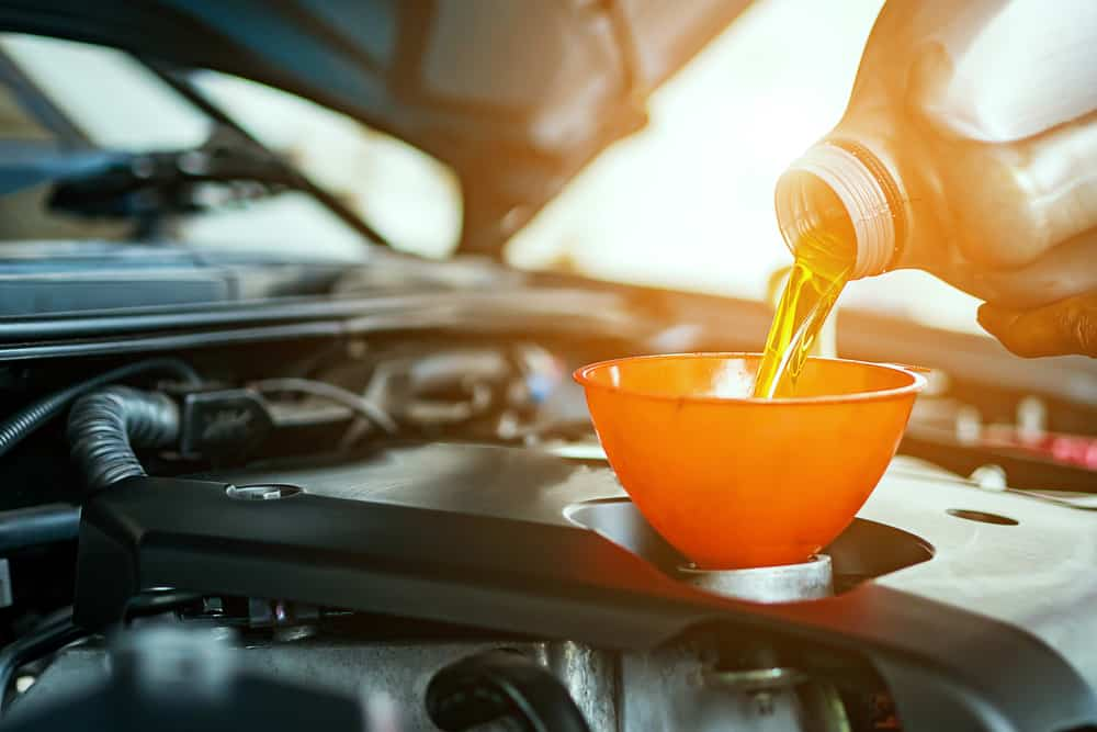 oil being poured into a vehicle's engine