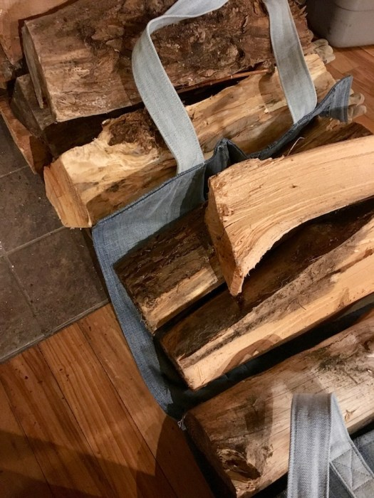 Pieces of firewood are stacked on top of a denim firewood sling, which is next to more wood stacked on the floor near a hearth.