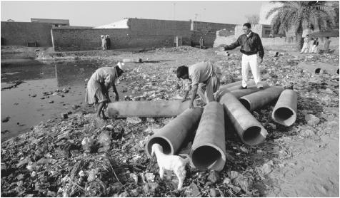 Workers on a community sanitation project examine the pipes for a new sewer in Faisalabad.