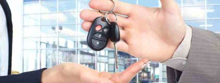 Salesman handing over the keys to the car of your dreams